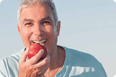 man eating apple after getting dental implants