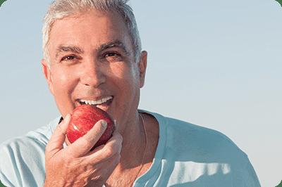 man eating apple after getting dental implants